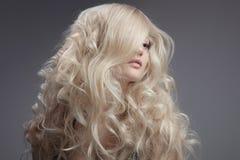 Schöne blonde Frau. Gelocktes langes Haar Lizenzfreie Stockbilder