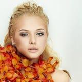 Schöne blonde Frau genießt ein Bad mit Blumen Stockfotografie