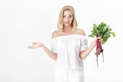 Schöne blonde Frau hält Rote-Bete-Wurzeln mit grünen Blättern auf weißem Hintergrund Gesundheit und Vitamine Lizenzfreie Stockfotos