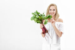 Schöne blonde Frau hält Rote-Bete-Wurzeln mit grünen Blättern auf weißem Hintergrund Gesundheit und Vitamine Stockfoto