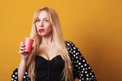 Schöne blonde Frau hält rote Papierschale mit dem Saft, der auf gelbem Hintergrund lokalisiert wird Stockfotografie