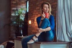 Schöne blonde Frau hält Tasse Kaffee beim Sitzen auf einer Tabelle gegen eine Backsteinmauer in einem Studio mit einem Dachboden Stockfotos