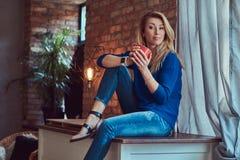 Schöne blonde Frau hält Tasse Kaffee beim Sitzen auf einer Tabelle gegen eine Backsteinmauer in einem Studio mit einem Dachboden Lizenzfreie Stockfotografie