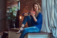 Schöne blonde Frau hält Tasse Kaffee beim Sitzen auf einer Tabelle gegen eine Backsteinmauer in einem Studio mit einem Dachboden Lizenzfreie Stockbilder