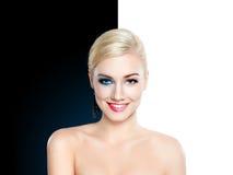 Schöne blonde Frau halb sauber und halbes Gesicht mit mak oben lizenzfreie stockfotografie
