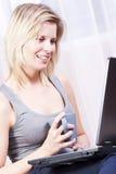 Schöne blonde Frau in ihrer Wohnung über dem Internet. Stockfotos