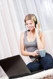 Schöne blonde Frau in ihrer Wohnung über dem Internet. Lizenzfreie Stockbilder