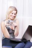 Schöne blonde Frau in ihrer Wohnung über dem Internet. Lizenzfreie Stockfotografie