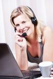Schöne blonde Frau in ihrer Wohnung über dem Internet. Stockbild