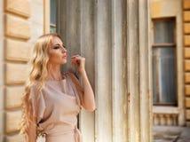 Schöne blonde Frau im beige langen Kleid Lizenzfreie Stockfotos