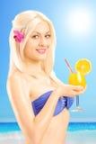 Schöne blonde Frau im Bikini, der ein Cocktail auf einem Strand hält Lizenzfreie Stockfotografie