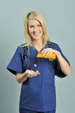 Schöne blonde Frau im Blau scheuert - Pillen Lizenzfreie Stockfotos