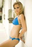 Schöne blonde Frau im blauen Bikini durch eine Wand Lizenzfreie Stockbilder