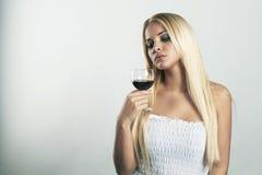 Schöne blonde Frau im blauen Kleid mit Glas Rotwein Lizenzfreie Stockfotos