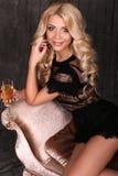 Schöne blonde Frau im eleganten Kleid, mit Glas Champagner Lizenzfreies Stockbild