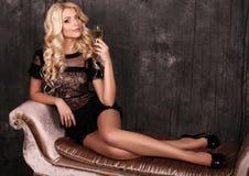 Schöne blonde Frau im eleganten Kleid, mit Glas Champagner Lizenzfreie Stockfotografie