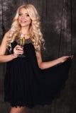Schöne blonde Frau im eleganten Kleid, mit Glas Champagner Stockfoto