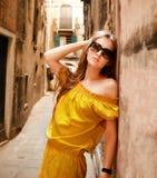 Schöne blonde Frau auf der Straße der alten Stadt Stockfoto