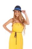 Schöne blonde Frau im gelben Kleid und in einem Hut Stockbild