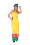 Schöne blonde Frau im gelben Kleid und in einem Hut Stockbilder