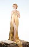 Schöne blonde Frau im Goldgewebe Lizenzfreie Stockfotografie