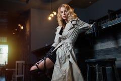 Schöne blonde Frau im grauen Mantel, der nahe Stangenzähler sitzt Stockbilder
