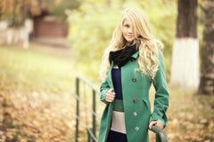 schöne blonde Frau im Herbstlaub Stockbild