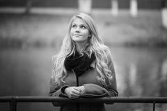 schöne blonde Frau im Herbstlaub Stockfotografie