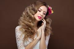 Schöne blonde Frau im Hochzeitskleid mit Abendmake-up, den zarten Lippen und den Locken Brautbild Schönes lächelndes Mädchen Stockfoto
