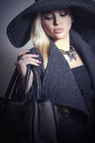 Schöne blonde Frau im Hut mit Handbag.Jewelry Stockfotografie