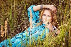 Schöne blonde Frau im Kleid liegt auf Gras Stockfoto