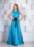 Schöne blonde Frau im langen blauen Kleid Stockfotos