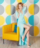 Schöne blonde Frau im langen blauen Kleid Stockbild