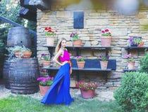 Schöne blonde Frau im langen bunten Kleid Stockfotografie