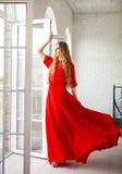 Schöne blonde Frau im langen Kleid Stockfotografie