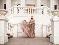 Schöne blonde Frau im langen Kleid draußen Stockfotografie