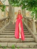 Schöne blonde Frau im langen Kleid draußen Stockbild