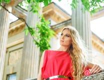 Schöne blonde Frau im langen roten Kleid Stockfotos