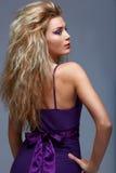 Schöne blonde Frau im purpurroten Kleid. Lizenzfreie Stockfotos