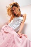 Schöne blonde Frau im rosafarbenen scirt. Stockbild