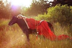 Schöne blonde Frau im roten Kleid am Pferd Stockbilder