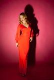 Schöne blonde Frau im roten langen Kleid Lizenzfreie Stockfotografie