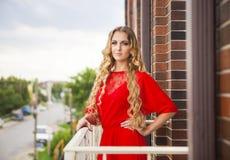 Schöne blonde Frau im roten langen Kleid Stockfotos