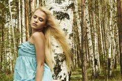 Schöne blonde Frau im russischen Wald. Fliegenhaar Stockbild