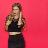 Schöne blonde Frau im schwarzen Kleid gegen rote Wand Lizenzfreie Stockbilder