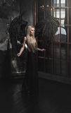 Schöne blonde Frau im schwarzen Kleid mit schwarzen Flügeln Stockfotografie