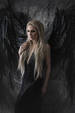 Schöne blonde Frau im schwarzen Kleid mit schwarzen Flügeln Stockbilder