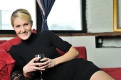 Schöne blonde Frau im schwarzen Kleid mit Wein Stockfoto
