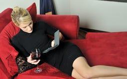 Schöne blonde Frau im schwarzen Kleid mit Wein Stockfotografie