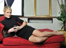 Schöne blonde Frau im schwarzen Kleid mit Wein Stockbilder